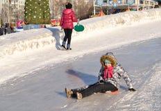 A menina desliza para baixo uma corrediça do gelo Imagem editorial Fotografia de Stock Royalty Free