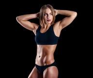 Menina desportiva com os grandes músculos no sportswear preto Mulher atlética nova bronzeada Um corpo fêmea do grande esporte imagem de stock