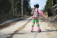 Menina desportiva da criança em patins de rolo imagens de stock