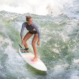 A menina desportiva de Atractive que surfa na onda artificial famosa do rio em Englischer garten, Munich, Alemanha Imagens de Stock Royalty Free