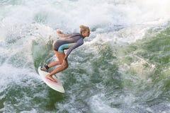 A menina desportiva de Atractive que surfa na onda artificial famosa do rio em Englischer garten, Munich, Alemanha Fotos de Stock