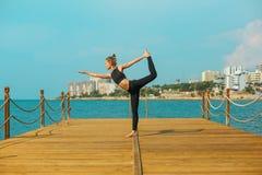 A menina desportiva está praticando a ioga no litoral Fotografia de Stock Royalty Free