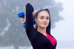 Menina desportiva nova que exercita com dumbells durante o worko do treinamento Imagem de Stock