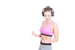 Menina desportiva que escuta a música e que faz o gesto do vencedor Foto de Stock