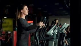 Menina desportiva que faz exerc?cios em um simulador especial do elipsoide vídeos de arquivo