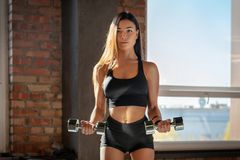 Menina desportiva que faz o exercício com pesos foto de stock royalty free