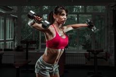 Menina desportiva que faz o exercício com pesos Foto de Stock