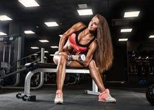 Menina desportiva que faz o exercício com pesos no gym fotografia de stock royalty free