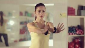 Menina desportiva que faz o exercício no gym na frente de vídeos de arquivo