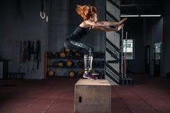 Menina desportiva que salta sobre algumas caixas em um gym do cruz-treinamento fotografia de stock royalty free