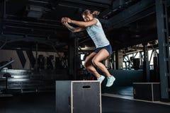Menina desportiva que salta sobre algumas caixas no gym foto de stock