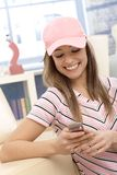Menina desportiva que usa o sorriso do telefone celular Fotos de Stock