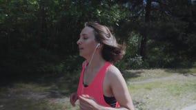 Menina desportivo atrativa na camisa cor-de-rosa que corre na mulher magro da floresta com o corpo treinado que faz exercícios A  filme