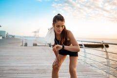 Menina desportivo bonita que olha o relógio durante o nascer do sol sobre o beira-mar imagem de stock