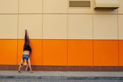 Menina desportivo em uma pose de cabeça para baixo em um fundo alaranjado Fotos de Stock Royalty Free
