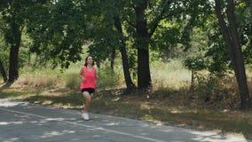 Menina desportivo nova na camisa cor-de-rosa e no short preto curto que correm no parque Mulher atrativa nos fones de ouvido com  video estoque