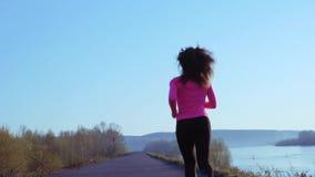 Menina desportivo que movimenta-se ao longo do banco de rio durante o nascer do sol ou o por do sol o conceito saudável do estilo video estoque