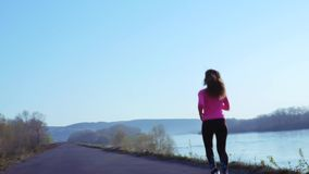 Menina desportivo que movimenta-se ao longo do banco de rio durante o nascer do sol ou o por do sol o conceito saudável do estilo vídeos de arquivo