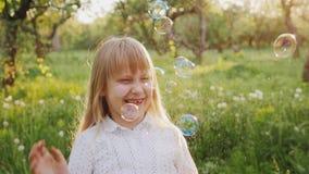 A menina despreocupada está travando bolhas de sabão alegremente Um jardim da caminhada na primavera filme