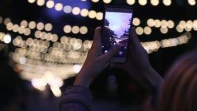 A menina dispara em um Natal e em um fundo do gerland das luzes da noite do smartphone