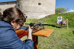 A menina dispara em uma besta das paredes da fortaleza em Staraya Imagem de Stock Royalty Free