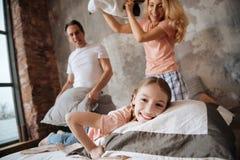 Menina divertida que tem a luta de descanso com pais em casa fotografia de stock royalty free
