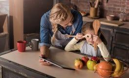Menina divertida que tem o divertimento com sua mãe na cozinha fotos de stock royalty free