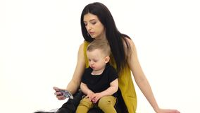 A menina diz e mostra algo no smartphone a sua criança Fundo branco video estoque