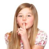 A menina diz seja quieta com seu dedo nos bordos imagens de stock