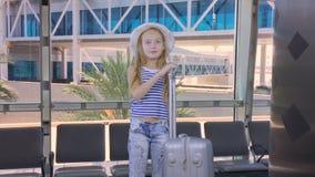 Menina do adolescente com o avião de espera da mala de viagem do curso na sala de estar da partida no aeroporto filme