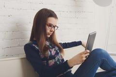A menina do adolescente com PC da tabuleta relaxa em casa imagens de stock