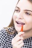 Menina do adolescente com suportes dos dentes usando a escova de dentes Interdental para limpar foto de stock