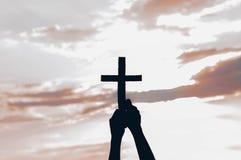 Menina do adolescente guardando a cruz à disposição durante o por do sol bonito M?os dobradas no conceito da ora??o para a f? foto de stock