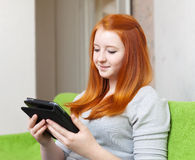 A menina do adolescente lê o eBook foto de stock