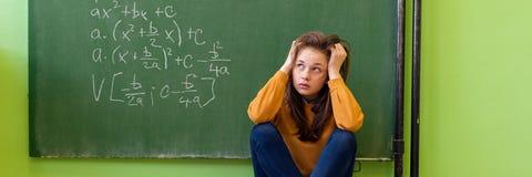 Menina do adolescente na classe da matemática oprimida pela fórmula da matemática Pressão, educação, conceito do sucesso imagens de stock