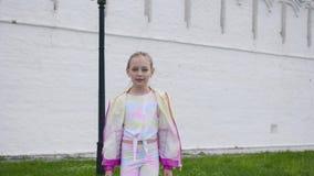 Menina do adolescente na roupa colorida que vai à câmera no fundo branco da parede Parte dianteira de levantamento e de passeio d filme