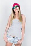 Menina do adolescente no short da sarja de Nimes e um t-shirt cinzento e um chapéu cor-de-rosa da malha, amarrados na camisa de m Imagem de Stock Royalty Free
