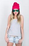 Menina do adolescente no short da sarja de Nimes e um t-shirt cinzento e um chapéu cor-de-rosa da malha, amarrados na camisa de m Fotografia de Stock