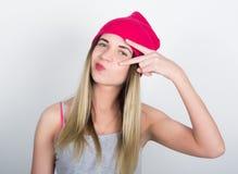 Menina do adolescente no short da sarja de Nimes e um t-shirt cinzento e um chapéu cor-de-rosa da malha, amarrados na camisa de m Foto de Stock