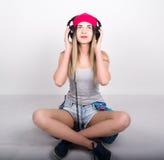 Menina do adolescente no short da sarja de Nimes e um t-shirt cinzento e um chapéu cor-de-rosa da malha, amarrados na camisa de m Fotos de Stock Royalty Free