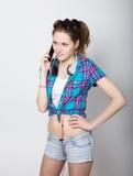 A menina do adolescente no short da sarja de Nimes e uma camisa de manta que falam no telefone celular e expressam emoções difere Foto de Stock