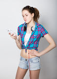 A menina do adolescente no short da sarja de Nimes e uma camisa de manta que falam no telefone celular e expressam emoções difere Imagens de Stock Royalty Free