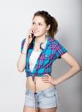 A menina do adolescente no short da sarja de Nimes e uma camisa de manta que falam no telefone celular e expressam emoções difere Fotos de Stock Royalty Free