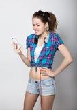 A menina do adolescente no short da sarja de Nimes e uma camisa de manta que falam no telefone celular e expressam emoções difere Imagens de Stock