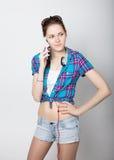 A menina do adolescente no short da sarja de Nimes e uma camisa de manta que falam no telefone celular e expressam emoções difere Fotografia de Stock Royalty Free