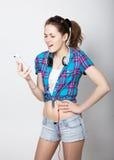 A menina do adolescente no short da sarja de Nimes e uma camisa de manta que falam no telefone celular e expressam emoções difere Foto de Stock Royalty Free