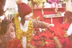 Menina do adolescente que compra a composição floral na feira do Natal Imagem de Stock Royalty Free