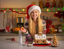 Menina do adolescente que decora a casa da cookie do Natal Foto de Stock