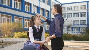 Menina do adolescente que fala com a mamã perto da faculdade A mamã e a filha adolescentes comunicam-se fora da faculdade após a  video estoque