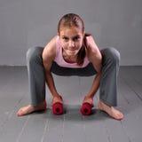 A menina do adolescente que faz exercícios com pesos para tornar-se com pesos muscles no fundo cinzento Retrato completo do compr Imagens de Stock